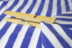 Wooden clothes peg. On a blue and white textile stock photo