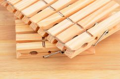 Wooden clothes pegs. On natural board background royalty free stock image