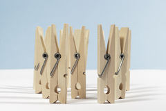 Wooden clothes pegs placed upright. Several spring-type wooden clothespins on white floor and blue background Stock Images