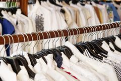 Clothes racks with hangers and with clothes on a blurred background inside shop. Wooden clothes racks with hangers and with clothes on a blurred background royalty free stock image