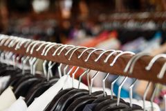 Clothes racks with hangers and with clothes on a blurred background inside shop. Wooden clothes racks with hangers and with clothes on a blurred background stock photos