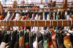 Wooden clothes racks with hangers and with colorful clothes. Wooden clothes racks with hangers and with colorful clothes inside a shop royalty free stock photography