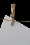 Wooden clothespin holding white paper on a wire. White paper sheet pinned bij a wooden clothespin on a sisal wire Royalty Free Stock Photos