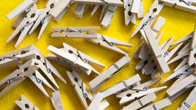 Wooden clothespin on yellow background. Many wooden clothespin on yellow background Royalty Free Stock Photos