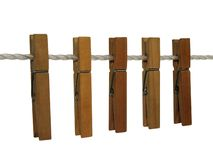 Wooden clothespins on a clothes line (+ clipping path). Wooden clothespins on a clothes line, isolated on white. Contains clipping path royalty free stock photos