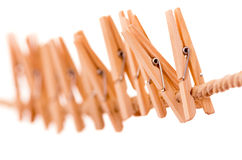 Wooden clothespins hanging on rope Stock Photo