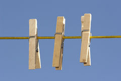 Wooden Clothespins Outdoors. Three spring type wooden clothespins in a row outdoors hanging on a clothes line Royalty Free Stock Photos