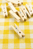 Wooden clothespins on yellow table cloth backgroun Stock Photography