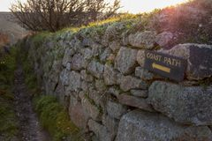 Wooden coast path sign in yellow writing hammered to a stone wall with view of coast path in distance at dawn Stock Image