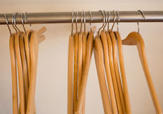 Wooden coat hangers on clothes rail Royalty Free Stock Images