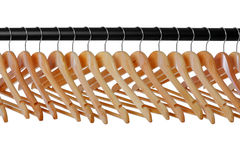 Wooden coat hangers on rail. A line of wooden coat hangers on a clothes rail stock image