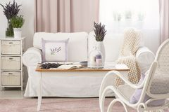 Wooden coffee table with pastel candles, fresh lavender and open book in real photo of bright sitting room interior with white cou royalty free stock photos