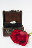 Wooden coffin with red rose and gold ring Royalty Free Stock Photos