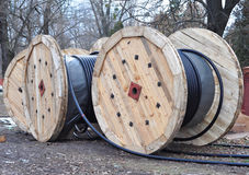 Wooden coil of electric cable and optical fibres on construction site. Stock Image