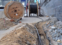 Wooden coil of electric cable and optical fibres in the digging on the street. Construction site Royalty Free Stock Images