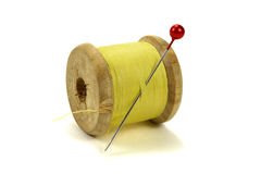 Wooden coil with threads and pin for sewing on a white background Royalty Free Stock Photography