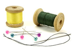 Wooden coils with threads, pins and needle for sewing on a white background Stock Photos