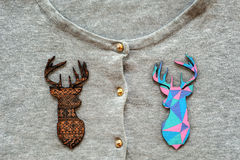 Wooden colored deers on grey pullover. As a background Royalty Free Stock Photos