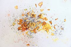 Wooden colored pencil sharpening shavings pile on white  background.  Royalty Free Stock Photo