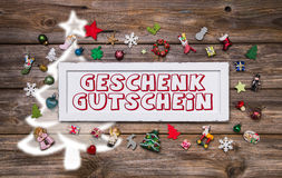 Wooden colorful christmas sign with text and decoration: gift ce Stock Images