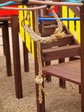 Wooden colorful construction on kinder playground, twisted rope on hanger. Stock Images