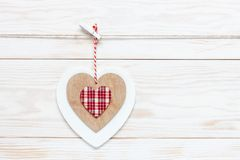Wooden colorful heart on rope. Concept for Valentine`s Day, wedding, engagement and other romantic events. Top view, close-up,. Flat lay on white wooden stock photo