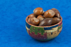Wooden colorful old bowl full of nuts Royalty Free Stock Images