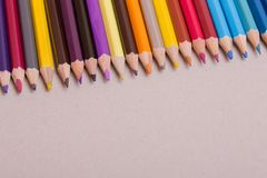 Colorful pencils. Wooden colorful pencils, on a grey paper royalty free stock images