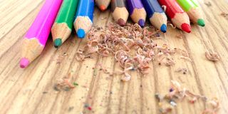Wooden colorful pencils with sharpening shavings, on wooden table. On wooden table Royalty Free Stock Images