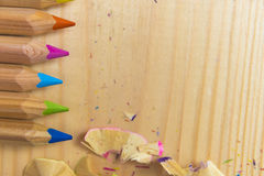 Wooden colorful pencils with sharpening shavings, on wooden table.  Stock Photos