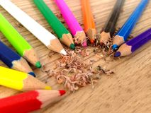 Wooden colorful pencils with sharpening shavings, on wooden table. On wooden table Royalty Free Stock Image