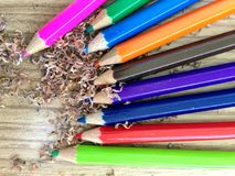 Wooden colorful pencils with sharpening shavings, on wooden table. On wooden table Royalty Free Stock Photo