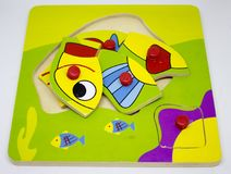 Wooden fish puzzle. Wooden colorful puzzle with fish for toddler Stock Photos