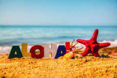 Wooden colorful word 'Aloha' on the sand Royalty Free Stock Image