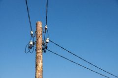 Wooden column with electric wires of natural color Stock Photos