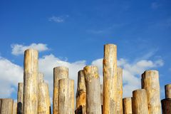 Wooden columns against cloudy blue sky Royalty Free Stock Photography