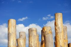 Wooden columns against cloudy blue sky Royalty Free Stock Photo