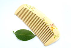 Wooden comb. Beautiful closeup shot of wooden comb with leaf Stock Photos