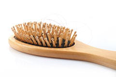 Wooden comb brush with lost hair. Isolated on white background Stock Photo