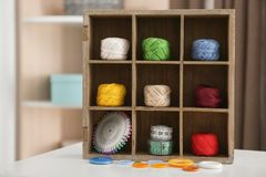 Wooden compartment box with crocheting. Clews and accessories on table indoors Royalty Free Stock Photo