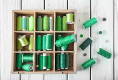 Wooden compartment box. With green sewing threads on table Stock Photo