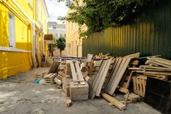 Wooden construction waste near fence and yellow wall Royalty Free Stock Images