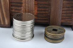 Wooden container with new and aged coins Stock Photo