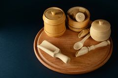 Wooden containers for products, spoon, cup, pestle, mortar on wo Stock Images