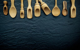 Wooden cooking utensils border . Wooden spoons and wooden scoops. On dark stone background with flat lay and copy space Stock Images