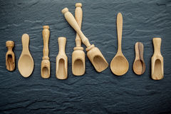 Wooden cooking utensils border . Wooden spoons and wooden scoops. On dark stone background with flat lay and copy space Stock Image