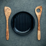 Wooden cooking utensils wooden spoons, spatula and black plate o. N dark background. Blank dish and copy space for menu design Stock Photography