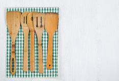 Wooden Cookingware and Cloth Napkin on white wood. Wooden spatula, spoons with striped cloth napkin on white wood. Horizontal layout with plenty of copy space Stock Images