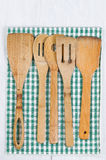 Wooden Cookware and cloth napkin on white wood. Wooden spatula, spoons with striped cloth napkin on white wood. Format in vertical layout Royalty Free Stock Photos