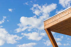 Wooden corner against the blue sky. And white clouds Royalty Free Stock Photos
